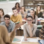 Large group of happy students having a class.